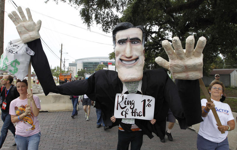 Protest marchers move with a puppet depicting Republican presidential candidate and former Massachusetts Gov. Mitt Romney during a march, Sunday, Aug. 26, 2012, in Tampa, Fla. Hundreds of protestors gathered in Gas Light Park in downtown Tampa to march in demonstration against the Republican National Convention. (AP Photo/Chris O'Meara)