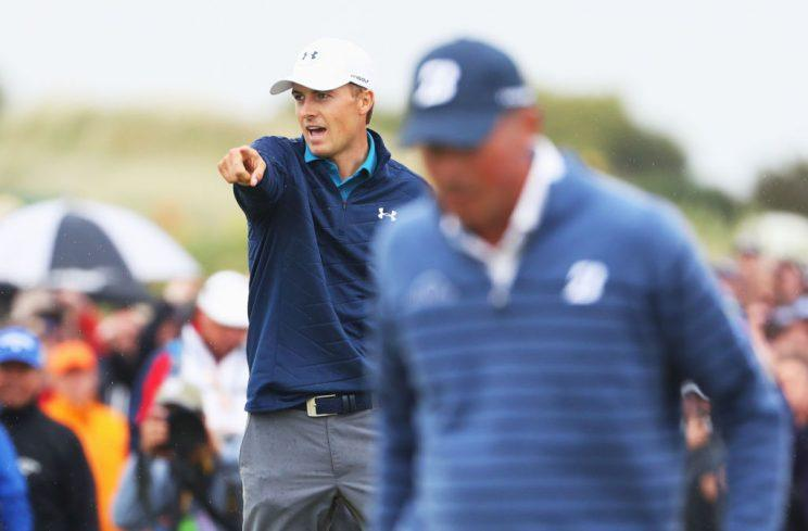 Jordan Spieth exults as Matt Kuchar walks past. (Getty)