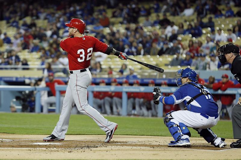 Los Angeles Angels' Josh Hamilton watches his three-run home run in front of Los Angeles Dodgers catcher A.J. Ellis during the first inning of an exhibition baseball game in Los Angeles, Friday, March 28, 2014. (AP Photo/Danny Moloshok)