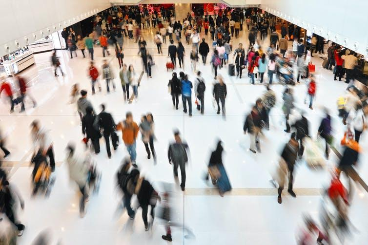 A busy shopping centre with many people walking around, some blurred