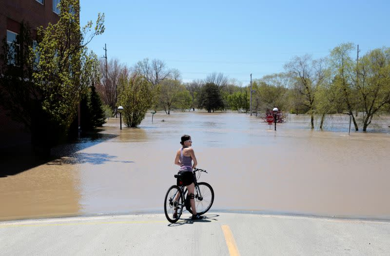 A resident looks at a flooded street along the Tittabawassee River, after several dams breached, in downtown Midland