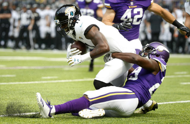 Jacksonville Jaguars wide receiver Marqise Lee is tackled by Minnesota Vikings defensive back Xavier Rhodes, right, during the first half of an NFL preseason football game, Saturday, Aug. 18, 2018, in Minneapolis. (AP Photo/Bruce Kluckhohn)