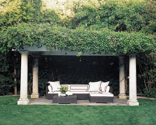 A pergola supported by four classical columns brings formal elegance to the garden of fashion designer Monique Lhuillier's Los Angeles home, which was decorated by Jennie Abbott. The sectional and cocktail table are by Dedon, and the tailored trim on the cushions and pillows gives a refined look to the outdoor room. (Photo: Roger Davies)