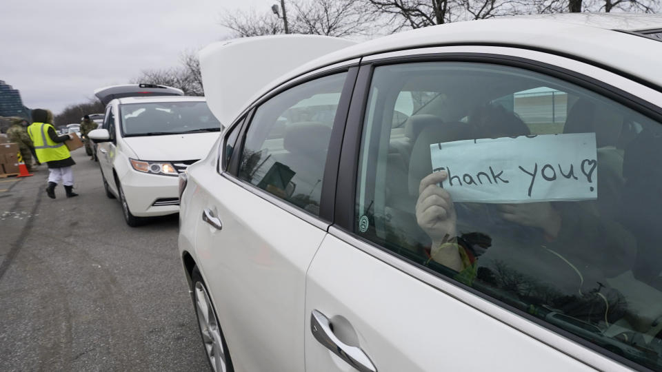"""A woman holds up a """"Thank You"""" sign as she gets her car loaded with groceries at a food bank distribution by the Greater Cleveland Food Bank, Thursday, Jan. 7, 2021, in Cleveland. (AP Photo/Tony Dejak)"""