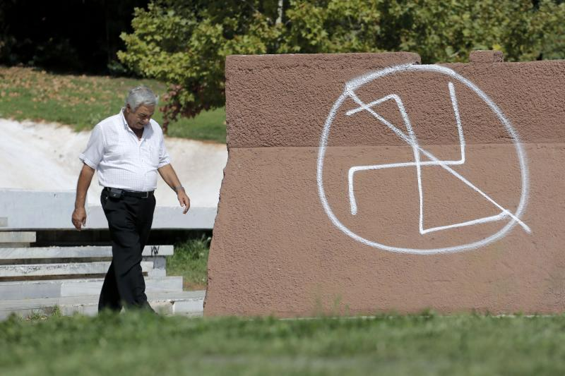 A pedestrian passes anti-fascist graffiti in Athens, Monday, Sept. 30, 2013. Greece's government is submitting legislation to Parliament aimed at cutting state funding to the extreme right-wing Golden Dawn party, whose leadership was arrested over the weekend on charges of acting as a criminal organization. (AP Photo/Petros Giannakouris)