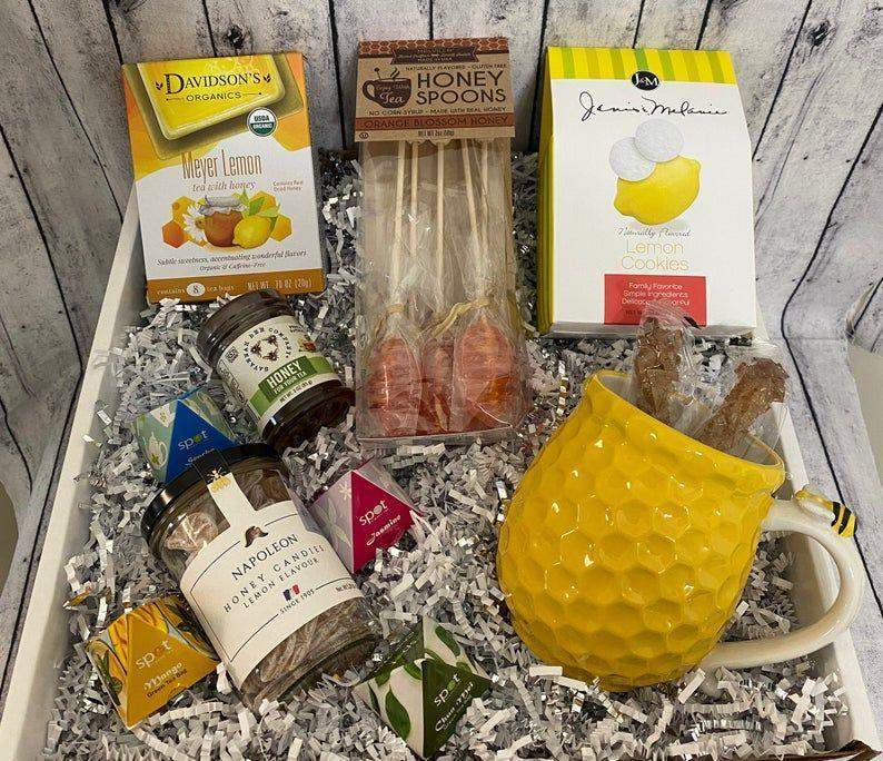 """<p><strong>TheGiftyGrape</strong></p><p>etsy.com</p><p><strong>$53.99</strong></p><p><a href=""""https://go.redirectingat.com?id=74968X1596630&url=https%3A%2F%2Fwww.etsy.com%2Flisting%2F990829362%2Ftea-and-honey-care-package-gift&sref=https%3A%2F%2Fwww.womansday.com%2Frelationships%2Ffamily-friends%2Fg35756207%2Fmothers-day-gift-baskets%2F"""" rel=""""nofollow noopener"""" target=""""_blank"""" data-ylk=""""slk:Shop Now"""" class=""""link rapid-noclick-resp"""">Shop Now</a></p><p>Does your mama prefer tea to coffee? Then get her this tea lovers' basket, which includes tea bags, honey stirrers, cookies, and a bee-themed mug. </p>"""