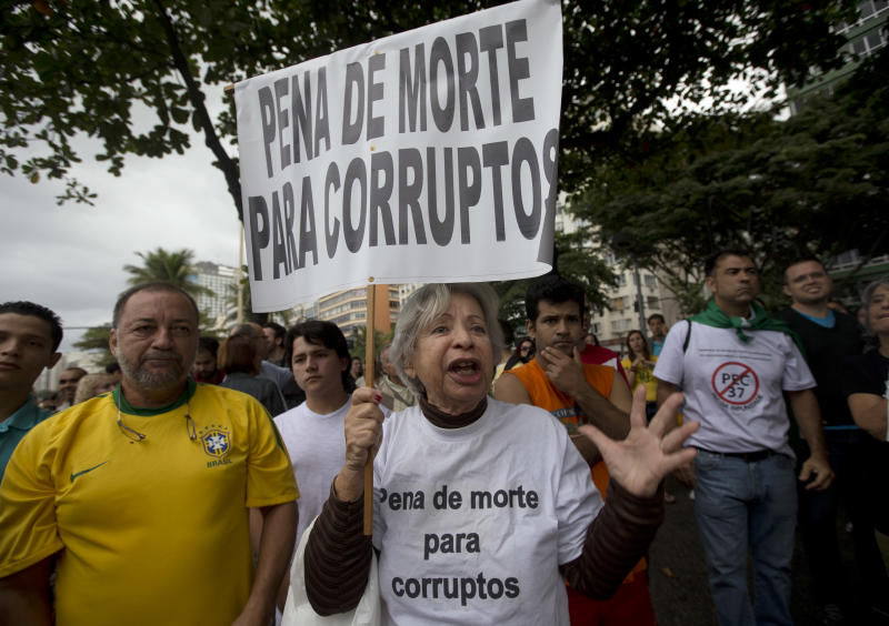 """A woman shouts while holding a poster that reads in Portuguese """"Death Penalty for Corrupt"""" during a protest at the Copacabana beach, in Rio de Janeiro, Brazil, Sunday, June 23, 2013. Protestors denounced a congressional legislation, known as PEC 37, that would limit the power of federal prosecutors to investigate crimes, which many fear would hinder attempts to jail corrupt politicians. The march is part a wave of protests that have shaken the nation and pushed the government to promise a crackdown on corruption and greater spending on social services. (AP Photo/Silvia Izquierdo)"""
