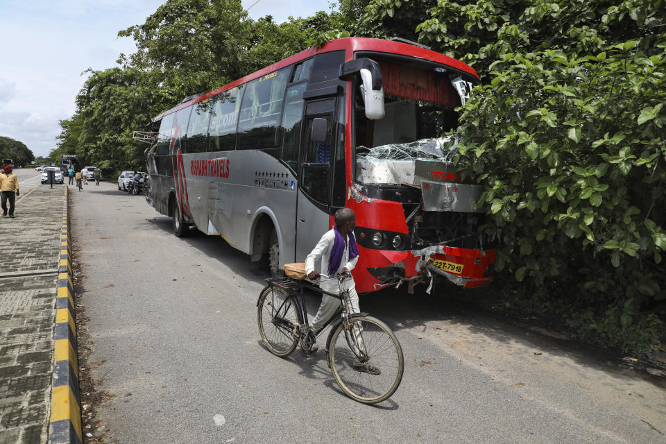 A man pushes his bicycle past a parked bus onto which a truck struck overnight in Barabanki, Uttar Pradesh state, India, Wednesday, July 28, 2021. Police say a truck struck a group of laborers sleeping under the parked bus on the side of a highway in northern India, killing more than a dozen of them. (AP Photo/Sumit Kumar)