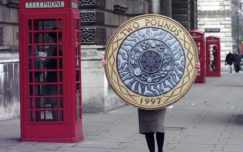 A cardboard replica of the new Two pound sterling coin is carried to the Treasury Dept - AP Photo/Lynne Sladky