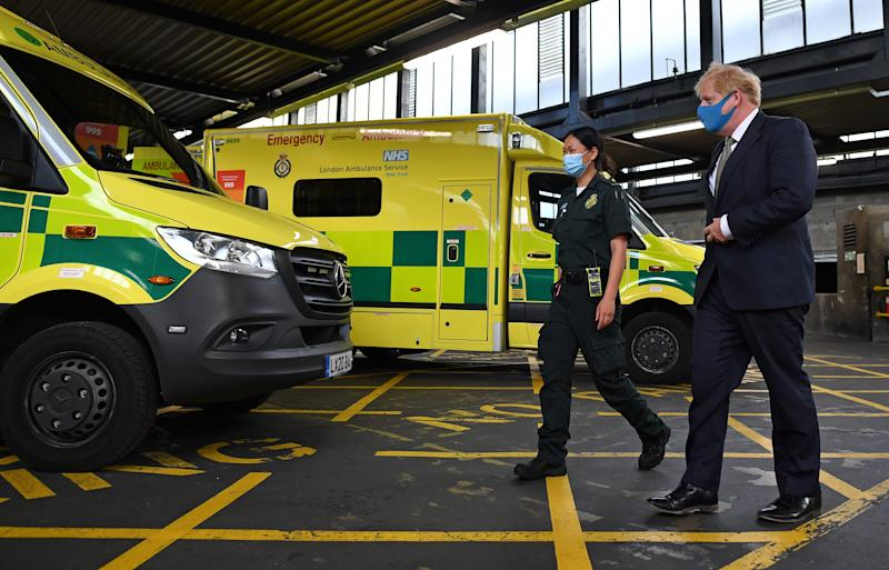 Prime Minister Boris Johnson, wearing a face mask, talks with paramedic Cindy Fu during a visit to the headquarters of the London Ambulance Service NHS Trust.