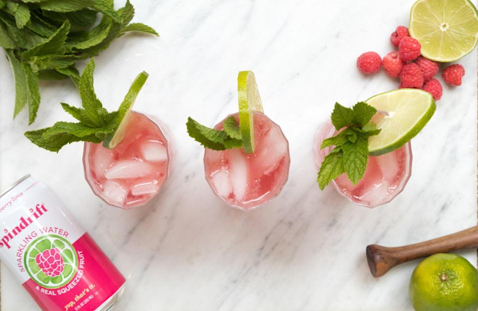 """<p>This low-calorie, fruity twist on a classic mojito by <a href=""""http://spindriftfresh.com/"""" class=""""link rapid-noclick-resp"""" rel=""""nofollow noopener"""" target=""""_blank"""" data-ylk=""""slk:Spindrift"""">Spindrift</a> can be made as a punch or per drink. </p> <p><strong>Ingredients:</strong></p> <ul> <li>0.5 oz. fresh lime juice </li> <li>Handful of fresh or frozen raspberries </li> <li>1 tsp. superfine sugar </li> <li>3 mint leaves (more for garnish) </li> <li>2 oz. white rum </li> <li>Spindrift Raspberry Lime</li> </ul> <p><strong>Directions:</strong> Muddle the raspberries with fresh lime juice and sugar in your glass. Add mint leaves and mush them into the glass to release the minty goodness, then add crushed ice and rum. Top it off with a low-calorie soda, such as Spindrift's Raspberry Lime, and garnish with whole raspberries, a sprig of mint, and a lime wheel. </p>"""
