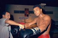 <p>Muhammad Ali gets his gloves laced outside a boxing ring in Houston, Texas in February 1967. Ali is training for a Feb. 6 championship title fight with Ernie Terrell. (AP Photo)</p>