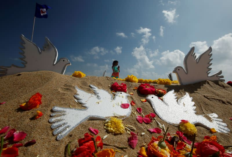A girl prays during a prayer ceremony for the victims of the 2004 tsunami on the 15th anniversary of the disaster, in Chennai