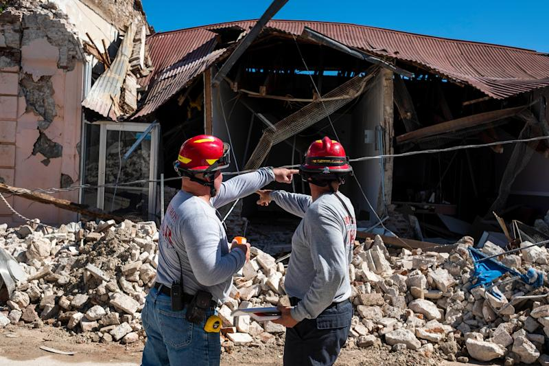 Two firemen survey a collapsed building after an earthquake hit the island in Guanica, Puerto Rico on January 7, 2020. - A strong earthquake struck south of Puerto Rico early January 7, 2020 followed by major aftershocks, the US Geological Survey said, the latest in a series of tremors that have shaken the island since December 28.