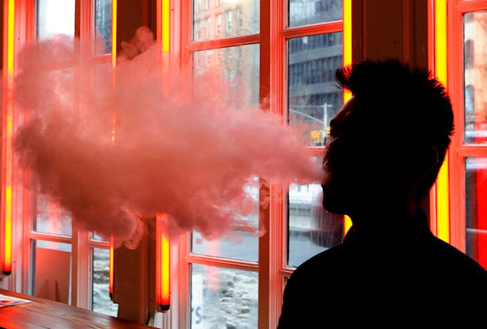 FILE - In this Feb. 20, 2014, file photo, a patron exhales vapor from an e-cigarette at a store in New York. Only two years ago e-cigarettes were viewed as holding great potential for public health: offering a way to wean smokers off traditional cigarettes. But now Juul and other vaping companies face an escalating backlash that threatens to sweep their products off the market. (AP Photo/Frank Franklin II, File)
