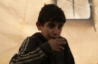 Mohammed Abu Rdan drinks tea inside a tent, at an internally displaced Syrian camp, in northern Aleppo