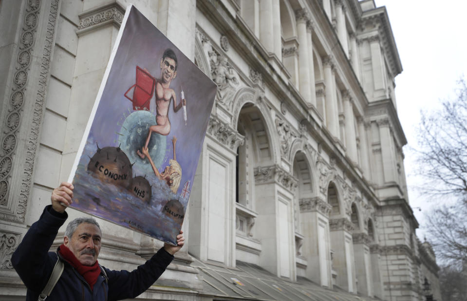 Artist Kaya Mar holds up his painting depicting Chancellor Rishi Sunak near Downing Street in London, Wednesday, March 3, 2021. Britain's Chancellor Rishi Sunak is expected to announce billions of pounds in tax cuts and spending increases to help workers and businesses hit by the coronavirus pandemic when he delivers his budget to Parliament on Wednesday. (AP Photo/Kirsty Wigglesworth)