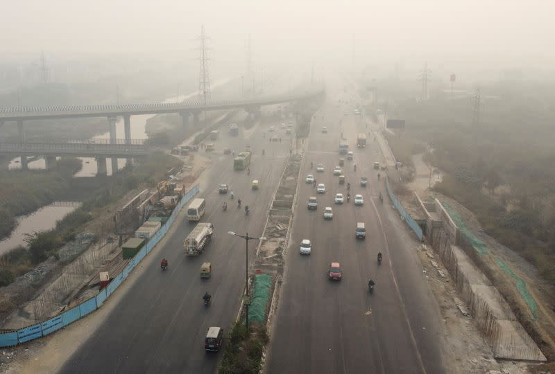 Traffic moves on a highway shrouded in smog in New Delhi