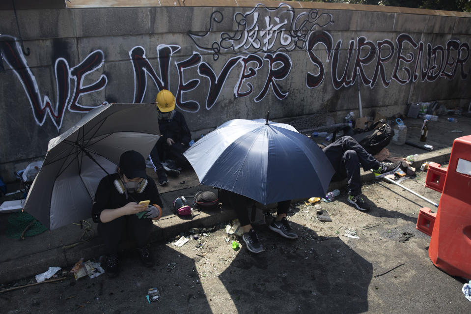 Pro-democracy protesters take rest on a bridge outside the Chinese University campus in Hong Kong, Wednesday, Nov. 13, 2019. Police increased security around Hong Kong and its university campuses as they brace for more violence after sharp clashes overnight with anti-government protesters. (AP Photo/Ng Han Guan)