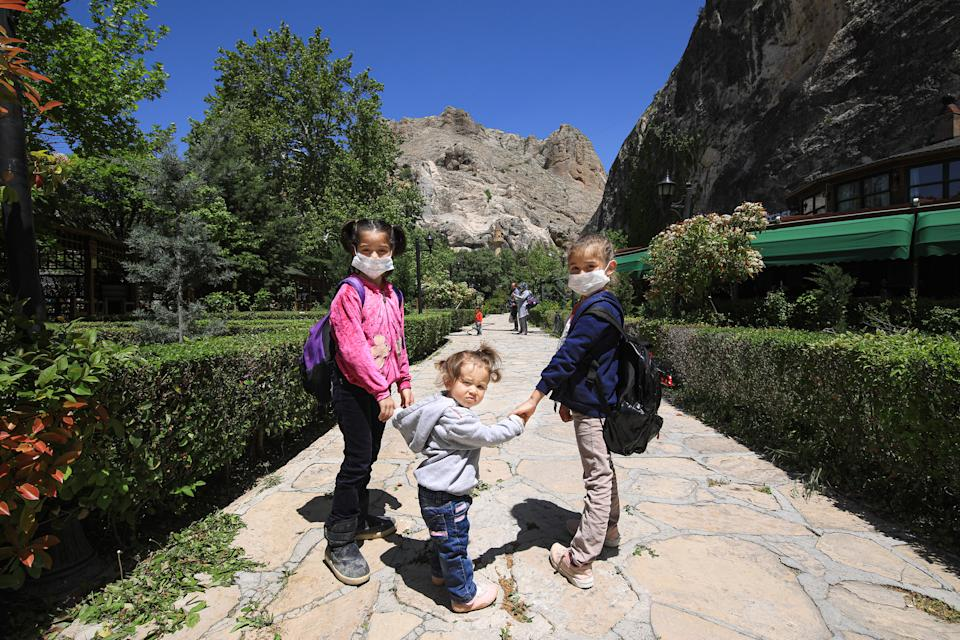 Kids play at the park in Tohma Canyon after children under 14 years across Turkey allowed to leave their homes, remaining within walking distance and wearing masks, on May 13 between 11 a.m. and 3 p.m. local time, in Malatya, Turkey on May 13, 2020. Turkey on Wednesday eased coronavirus (Covid-19) restrictions for young people under 14 years old. (Photo by Ayhan Iscen/Anadolu Agency via Getty Images)