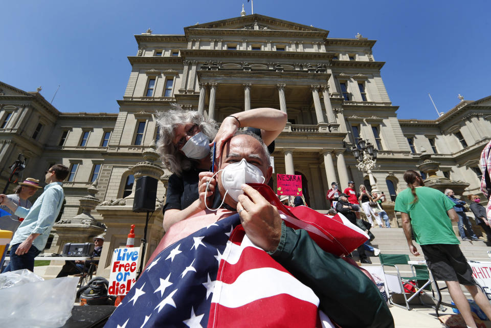 Annette Rafacz gives Manny Orovcoa a free haircut at the State Capitol during a rally in Lansing, Mich., Wednesday, May 20, 2020. Barbers and hair stylists are protesting the state's stay-at-home orders, a defiant demonstration that reflects how salons have become a symbol for small businesses that are eager to reopen two months after the COVID-19 pandemic began. (AP Photo/Paul Sancya)