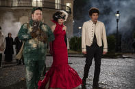 """This image released by Disney shows Paul Walter Hauser, Emma Stone and Joel Fry in a scene from """"Cruella."""" Costumes for the film were designed by Oscar winning designer Jenny Beavan. (Laurie Sparham/Disney via AP)"""