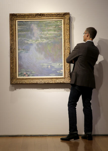 """A man gets a closer look at """"Nympheas"""" by Claude Monet during an auction preview at Christie's in New York, Tuesday, May 6, 2014. Works from the estates of heiress Huguette Clark, Edgar Bronfman and other major collectors are leading New York City's spring art auctions. The sale of impressionist and modern art begins Tuesday evening at Christie's. The auction house says it expects to raise over $245 million. (AP Photo/Seth Wenig)"""