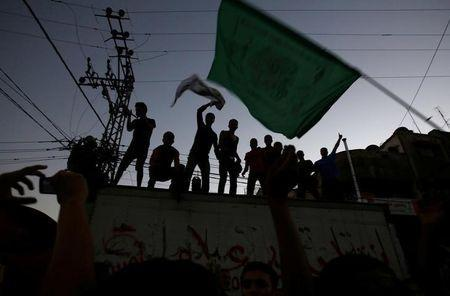 FILE PHOTO - A Palestinian waves a Hamas flag (R) in Gaza City August 26, 2014. REUTERS/Suhaib Salem/File Photo