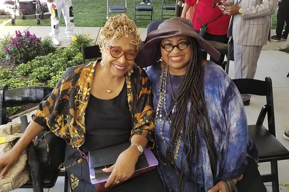 In this 2019 photo provided by Marsha Battle Philpot, Philpot, right, widely known by her moniker Marsha Music and Brenda Perryman pose for a photo at the groundbreaking ceremony for the Motown Museum expansion in Detroit. As the coronavirus tightened its grip across the country, it is cutting a particularly devastating swath through an already vulnerable population, black Americans. The coronavirus deaths in Detroit include educator and playwright Perryman and Gloria Smith, who was a staple at the city's African World Festival and died within a week of her husband. (Marsha Battle Philpot via AP)
