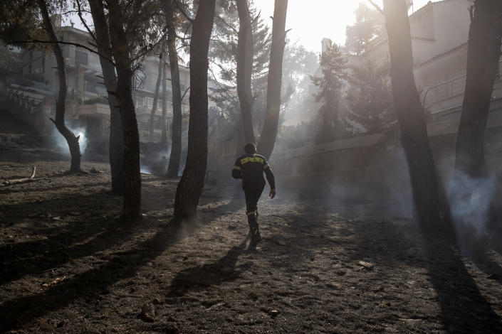 A firefighter makes his way through burnt trees following a forest fire at Dionysos northern suburb of Athens, on Tuesday, July 27, 2021. Greek authorities have evacuated several areas north of Athens as a wildfire swept through a hillside forest and threatened homes despite a large operation mounted by firefighters. (AP Photo/Yorgos Karahalis)