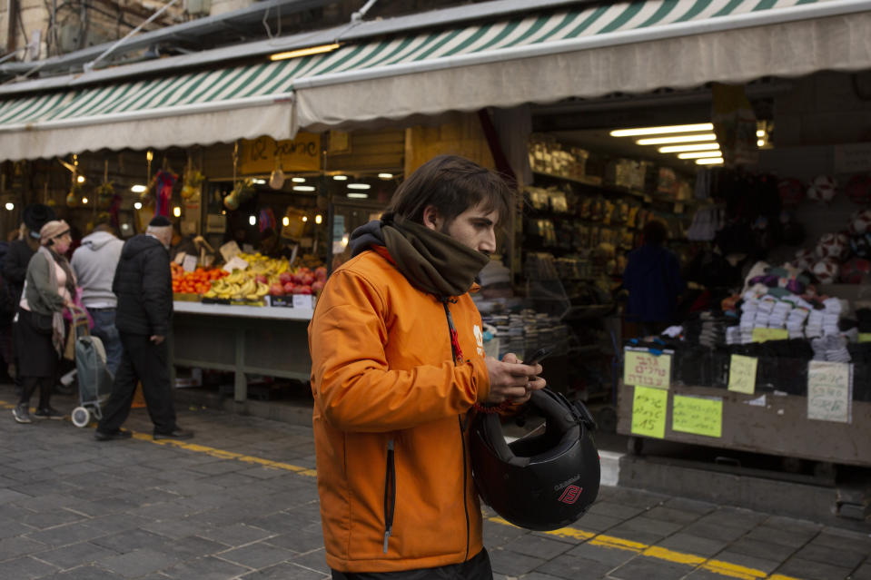 A dood delivery driver carries his smart phone in the Mahane Yehuda market in Jerusalem, Wednesday, Dec. 23, 2020. In the early days of the pandemic, a panicked Israel began using a mass surveillance tool on its own people, tracking civilians' mobile phones to halt the spread of the coronavirus. But months later, the tool's effectiveness is being called into question and critics say its use has come at an immeasurable cost to the country's democratic principles. (AP Photo/Maya Alleruzzo)