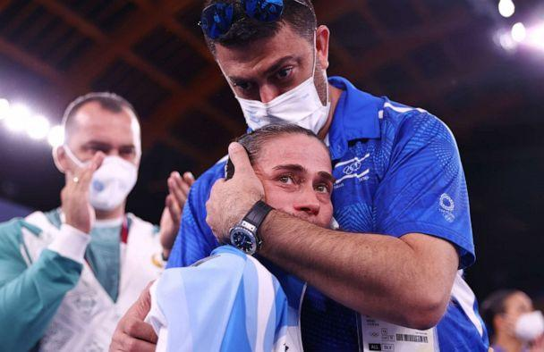 PHOTO: Oksana Chusovitina of Uzbekistan is embraced by Orabi Bader, physiotherapist for Israel, after performing on the vault on July, 25, 2021 in Tokyo. (Lindsey Wasson/Reuters)