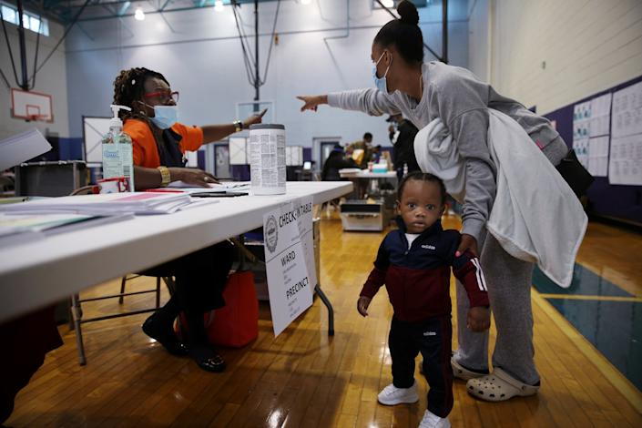 A Black woman and her small son receive instructions from a Black poll worker in a gym set up for voting