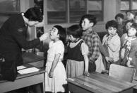Nurse Desrochers checks a girl's throat while other children wait in line, at the Frobish Bay Federal Hostel in Iqaluit, Nunavut, in a 1959 archive photo. REUTERS/H. Leclair/Canada. Health and Welfare Canada collection/Library and Archives Canada/e002504641/handout
