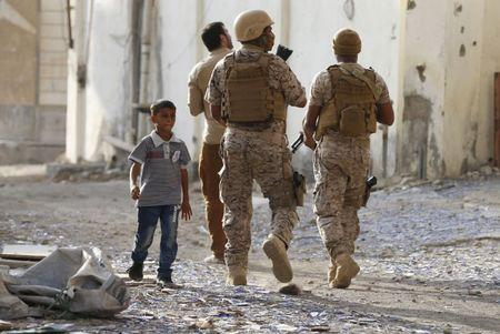 Boy walks past soldiers from the Saudi-led coalition patrolling a street in Yemen's southern port city of Aden