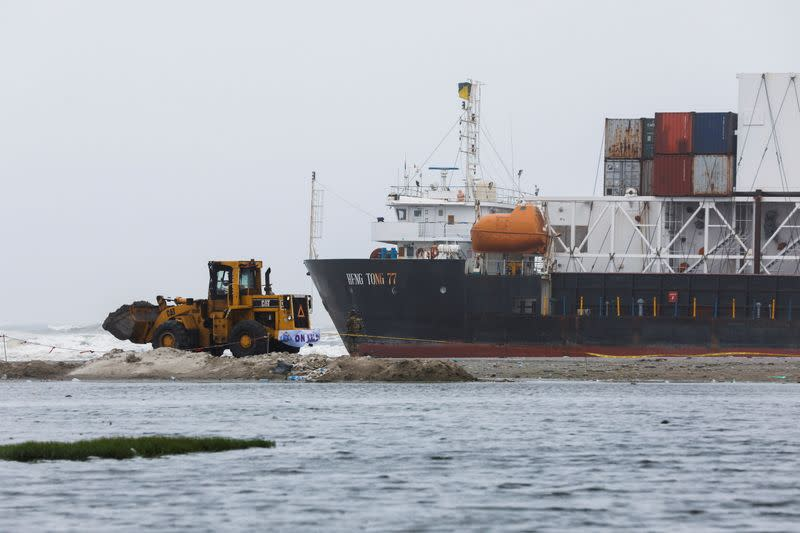 A wheel loader clears the ground near stranded cargo ship MV Heng Tong 77 at Sea View beach in Karachi