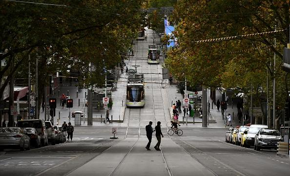 Pedestrians cross a deserted street in Melbourne's central business district as Australia starts to ease its COVID-19 coronavirus restrictions.