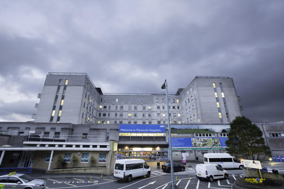 Plymouth, United Kingdom - July 16, 2012: Derriford Hospital was build in 1981 and is a large teaching hospital covering health care for the southwest of England. The photograph shows the main entrance to the hospital on a dark overcast day. Vehicles can be seen parked up with people visible in the entrance.