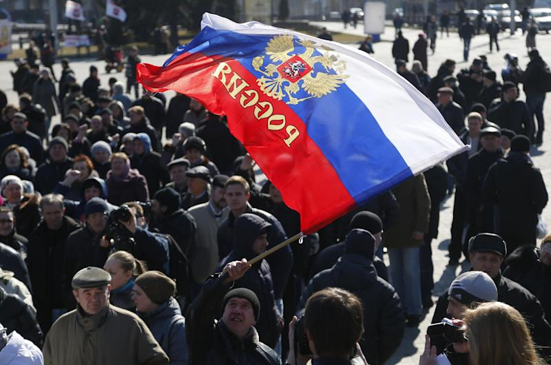 A man waves a Russian flag during a pro Russian rally at a central square in Donetsk, eastern Ukraine, Monday, March 10, 2014. Many Russian-speakers in the region continue to protest against the new Ukrainian government following the overthrow of pro-Kremlin President Viktor Yanukovych. (AP Photo/Sergei Grits)