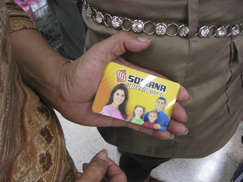 A woman shows her pre-paid gift card while waiting in line at a Soriana supermarket in Mexico City, Tuesday July 3, 2012. Many of the people at the supermarket say they went to redeem pre-paid gift cards they said were given them by the party that won Mexico's presidency and at least a few cardholders were angry, complaining they didn't get as much as promised, or that their cards weren't working. The incidents are inflaming accusations that the election was marred by massive vote-buying. (AP Photo/Marco Ugarte)