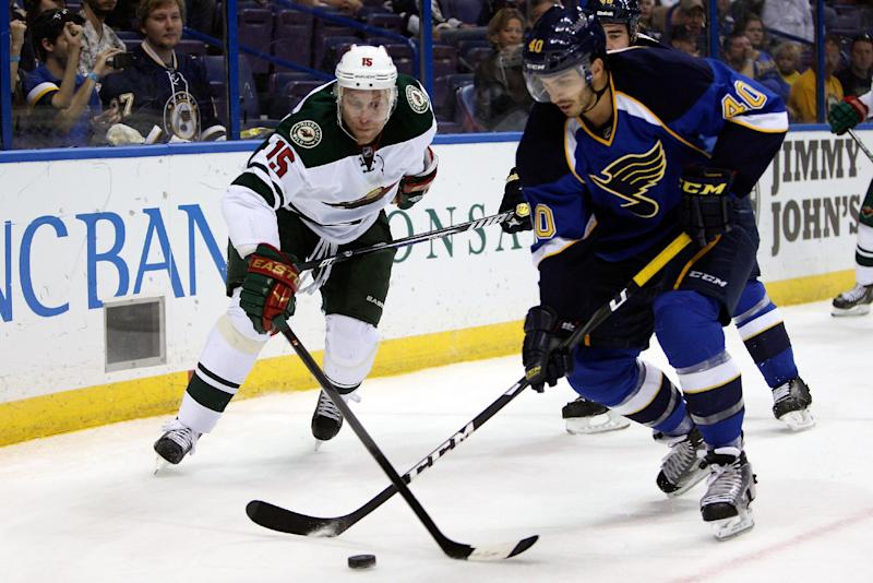Minnesota Wild's Dany Heatley (15) of Germany, and St. Louis Blues' Maxim Lapierre (40) battle for control of the puck during the first period of a preseason NHL hockey game Friday, Sept. 27, 2013, in St. Louis. (AP Photo/Scott Kane)