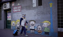 A woman past a mural featuring characters from the comic strip character Mafalda created by Argentine cartoonist Joaquin Salvador Lavado, who was better known as Quino, in Buenos Aires, Argentina, Wednesday, Sept. 30, 2020. Lavado passed away on Wednesday, according to his editor Daniel Divinsky who announced it on social media. He was 88. (AP Photo/Victor R. Caivano)