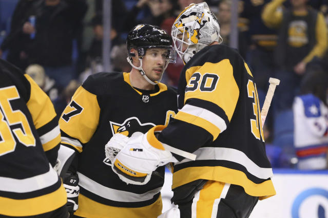 Pittsburgh Penguins forward Sidney Crosby (87) and goalie Matt Murray celebrate a 4-2 victory over the Buffalo Sabres in an NHL hockey game Thursday, March 5, 2020, in Buffalo, N.Y. (AP Photo/Jeffrey T. Barnes)