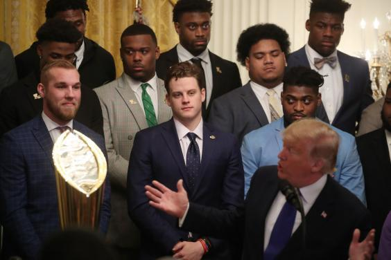 Members of the LSU Tigers look on as Donald Trump makes jokes at a reception for them in the East Room of the White House to reward their victory in the college football playoff final (Getty Images)