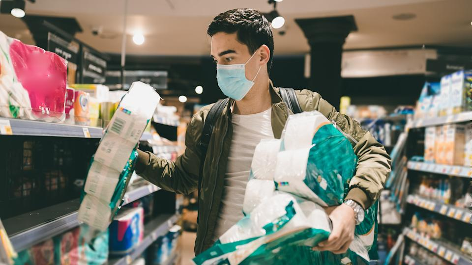 Young Man shopping in a supermarket, breathing through a medical mask because of the danger of getting the flu virus, influenza infection.