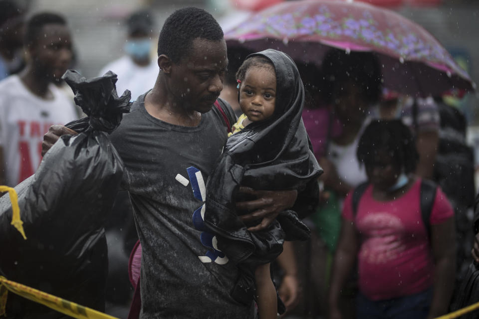 A Haitian migrant carries a baby to a boat that will take them to Capurgana, on the border with Panama, from Necocli, Colombia, early Thursday, July 29, 2021. Migrants have been gathering in Necocli as they move north towards Panama on their way to the U.S. border. (AP Photo/Ivan Valencia)