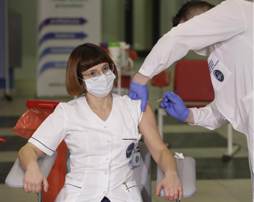 Alicja Jakubowska,left, the head nurse at the Interior Ministry hospital in Warsaw, is getting the coronavirus vaccination by doctor, Artur Zaczynski, right, in Warsaw, Poland, Sunday Dec. 27, 2020. Jakubowska was the first person to be vaccinated in Poland as part of a European Union rollout on Sunday. in Warsaw, Poland, Sunday, Dec. 27, 2020. (AP Photo/Czarek Sokolowski)