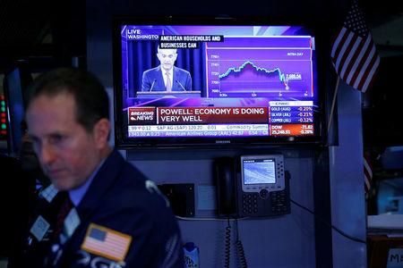 Traders work on the floor of the New York Stock Exchange (NYSE) as a TV screen shows the Fed Rate hike announcment in New York City