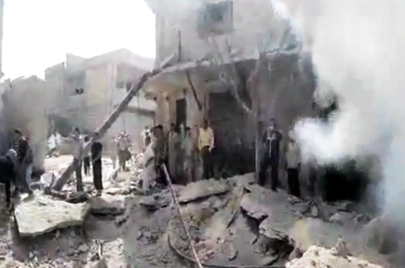In this image made from amateur video released by the Shaam News Network and accessed Tuesday, Aug. 28, 2012, Syrian men stand in the rubble of a destroyed building from purported airstrikes in Kfarnebel, Idlib province, northern Syria. (AP Photo/Shaam News Network via AP video) THE ASSOCIATED PRESS IS UNABLE TO INDEPENDENTLY VERIFY THE AUTHENTICITY, CONTENT, LOCATION OR DATE OF THIS HANDOUT PHOTO