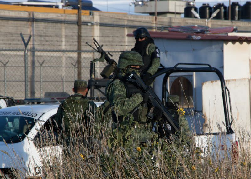 Members of the Mexican National Guard stand atop a vehicle as they keep watch outside the prison after sixteen inmates were killed and five were wounded in a prison fight at the Regional Center for Social Reintegration in the town of Cieneguillas